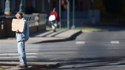 In this Thursday, Oct. 15, 2015, file photo, a man holds a placard while soliciting motorists for work at a major intersection just south of downtown Denver. Cities trying to limit panhandling in downtowns and tourists areas are facing a new legal hurdle because of a recent Supreme Court ruling that seemingly has nothing to do with asking for money. (AP Photo/David Zalubowski, file)