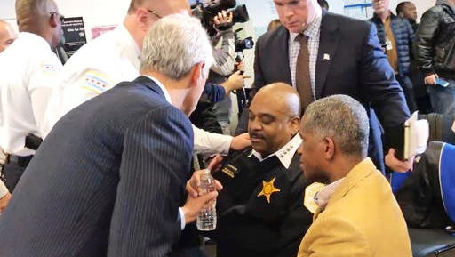 In this photo taken from video, Chicago Mayor Rahm Emanuel, left, hands a bottle of water to Police Superintendent Eddie Johnson after Johnson became wobbly during a news conference Friday, Jan. 27, 2017 in Chicago. The Chicago Sun-Times reports that there were requests for candy for Johnson as he fell ill. The news conference was halted as Johnson was attended to and an ambulance and a fire truck arrived.