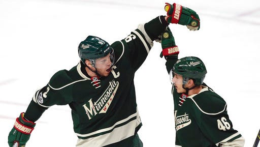 Minnesota Wild center Mikko Koivu (9), of Finland, congratulates defenseman Jared Spurgeon (46) on a goal against the Colorado Avalanche during the first period of an NHL hockey game Sunday in St. Paul.