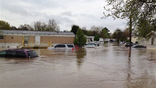 Flood waters cover a street in a mobile home park in Pelham, Ala., on Monday, April 7, 2014. Police and firefighters rescued about a dozen people who were trapped by muddy, fast-moving water after storms dumped torrential rains in central Alabama. (AP Photo/Jay Reeves)
