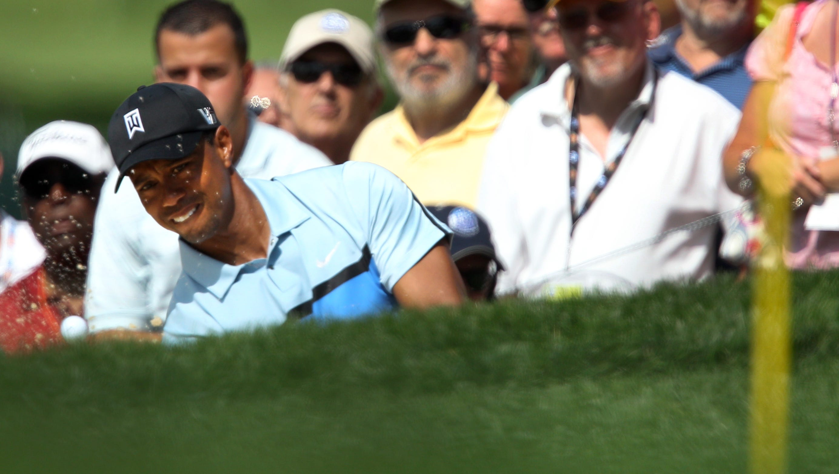 Tiger Woods watches as his ball drops onto the 18 green during the first round of the 95th PGA Championship at Oak Hill in Pittsford, NY August 8, 2013.