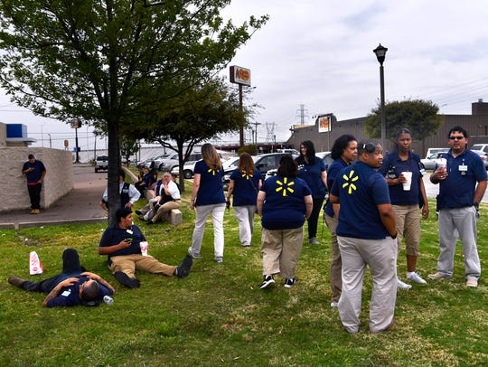 Walmart employees wait on the edge of the north side