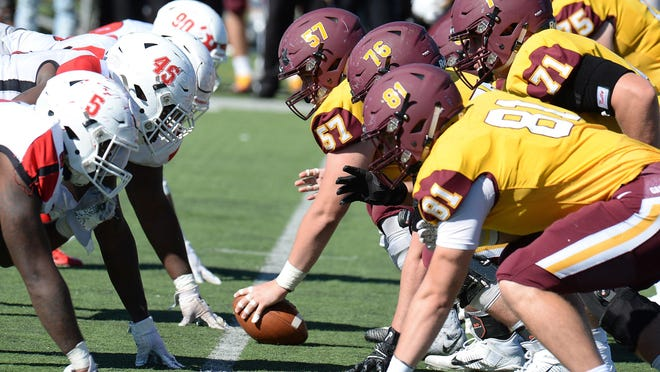 The Edinboro University, left, and Gannon University football teams line up at McConnell Family Stadium in Erie on Oct. 5, 2019.