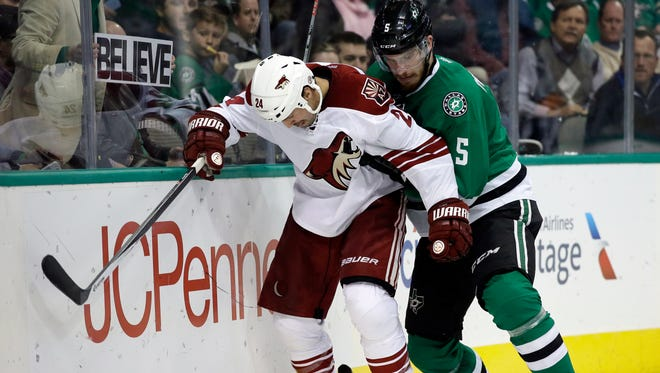 Arizona Coyotes' Kyle Chipchura (24) and Dallas Stars' Jamie Oleksiak (5) compete for control of a puck up in the second period of an NHL hockey game, Thursday, Nov. 20, 2014, in Dallas.