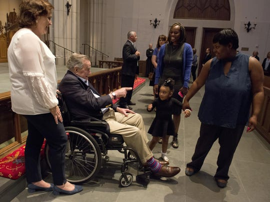Former President George H. W. Bush greets the mourners