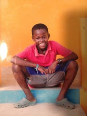 Rivaldo Hill is shown as a boy in Haiti. He was taken