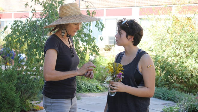 Cathy Law, environmental science teacher at New Paltz High School, advises Mariabella Todaro, a student in the environmental club, as she arranges flowers cut from the courtyard gardens.