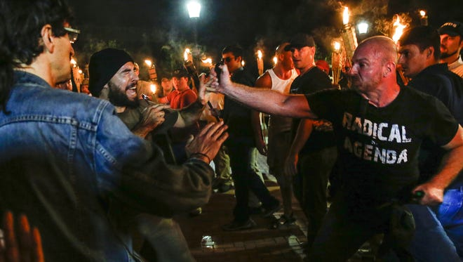 White nationalist Christopher Cantwell, right, pepper sprays a counterprotester on the University of Virginia campus in Charlottesville on Friday, August 11, 2017. Multiple white nationalist groups marched with torches through the campus until they were met with counter protest.  Mandatory Credit: Mykal McEldowney/IndyStar via USA TODAY NETWORK
