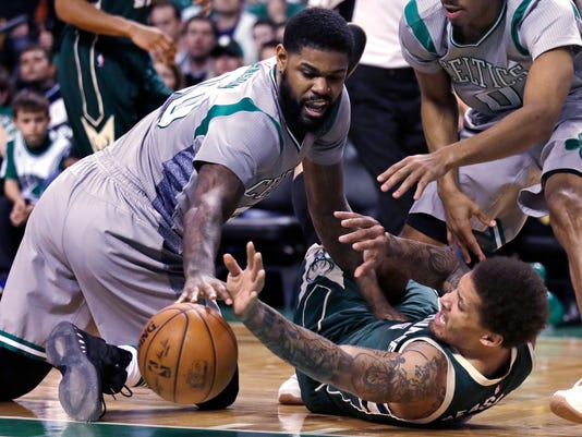 Milwaukee Bucks forward Michael Beasley, right, battles for a loose ball with Boston Celtics forward Amir Johnson (90) during the second half of an NBA basketball game in Boston, Wednesday, April 12, 2017. (AP Photo/Charles Krupa)