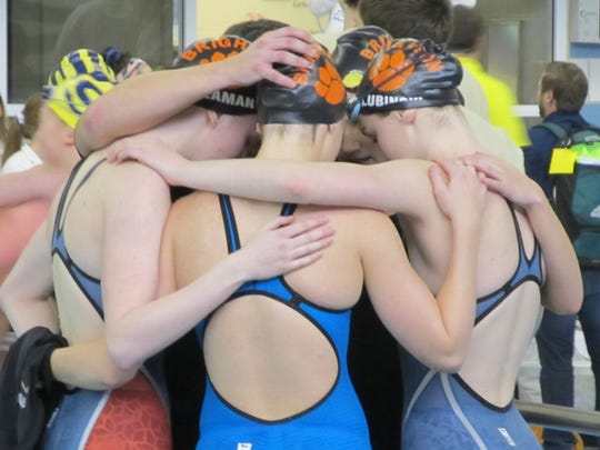 Brighton's 400-yard freestyle relay team gathers with coach Jason Black after placing fifth in the final event of the state Division 1 meet.