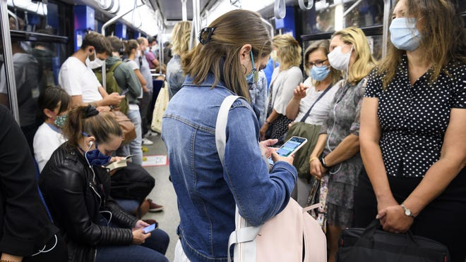 """People wearing protective mask ride the """"Transports publics lausannois"""", TL, Metro M2 (underground) during the coronavirus disease (COVID-19) outbreak, in Lausanne, Switzerland, Monday, July 6, 2020. In Switzerland, from Monday 6 July, people aged 12 and over must wear a mask in all public transport, trains, trams and buses, as well as in cable cars and boats."""