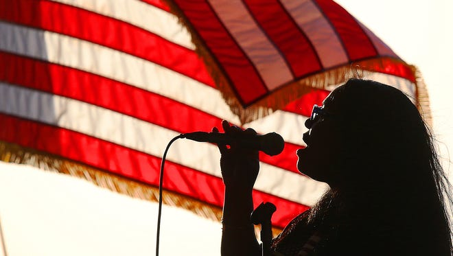 Yvetta Dominique sings the national anthem on Sunday during the Tribute to American Heroes event at Centenneial Park in downtown Fort Myers. The ceremony featured a 21-gun salute, music by the Southwest Florida Symphony and wreath laying in honor of service men and women who died.
