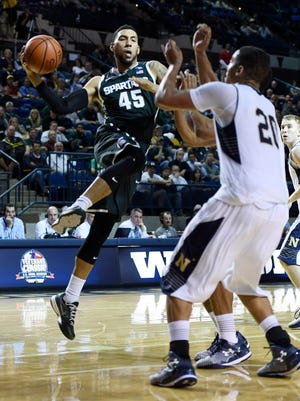 Michigan State's Denzel Valentine, left, drives to the basket as Navy's Shawn Anderson defends during the second half Friday night.