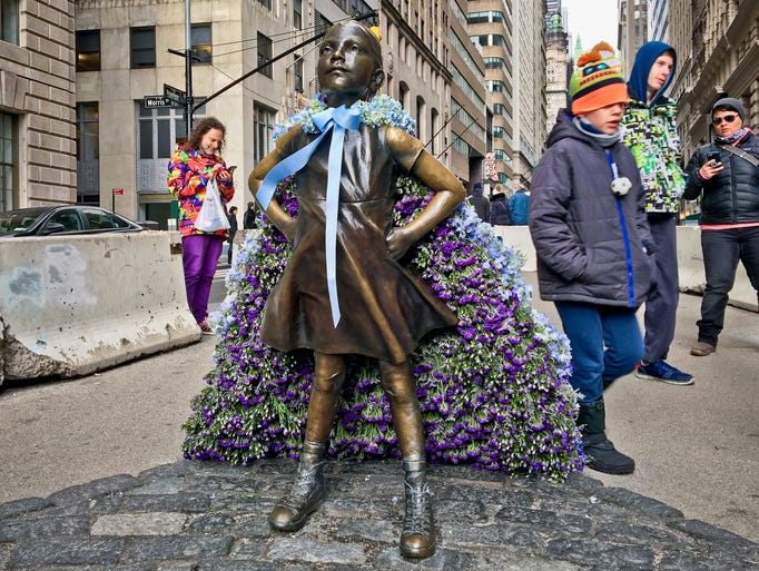 """Wall Street's """"Fearless Girl"""" statue is draped with"""