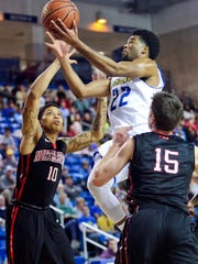 Delaware's Cazmon Hayes drives between Northeastern's T.J. Williams (left) and Caleb Donnelly in the first half of Delaware's 69-60 loss at the Bob Carpenter Center Saturday.