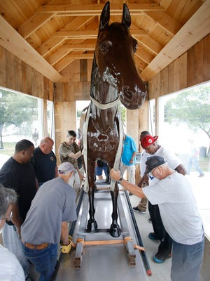 Eldridge Park Carousel Preservation Society members and volunteers work to install the American Girl statue at the park Wednesday. The life-size horse statue, which honors the race horse that died on the Elmira racetrack, was put back together after vandals destroyed it in 1980.