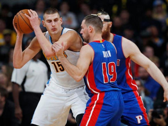 Denver Nuggets forward Nikola Jokic, left, is trapped