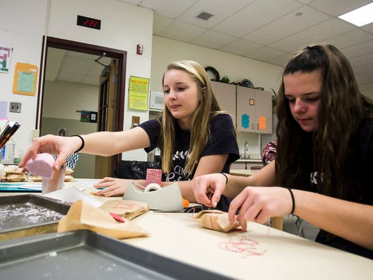 "From left, Central York Middle School eighth-graders Emma Gladfelter and Jillian Krentz package and wrap lavender lemon heart fizzles Wednesday, Feb. 1, 2017, during their Central Relaxation class. Central Relaxation is a student run business. Students have developed ""fizzles"" and other relaxation products that are currently being sold online and in business. Amanda J. Cain photo"