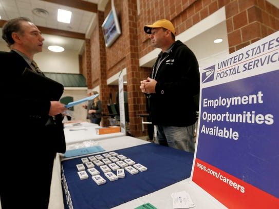 A recruiter from the postal service, right, speaks