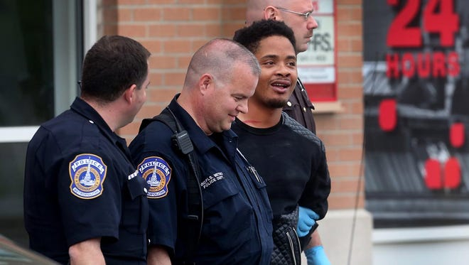 Police take away a suspect in the attempted robbery of a CVS at 16th and Meridian streets on Monday.