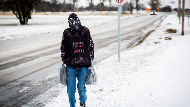 Nathaniel Crisp abandons waiting for the bus on the southside of Muncie to walk home in his zipped up Darth Vadar hoodie as he attempts to limit his exposure to freezing temperatures Tuesday morning.