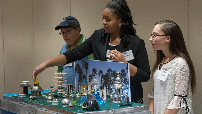 Eighth-graders Edward Austin, Ariyon Toney and Malena Smith explain their city, Kutali, to judges. They are from St. Valentine School in Redford Township.