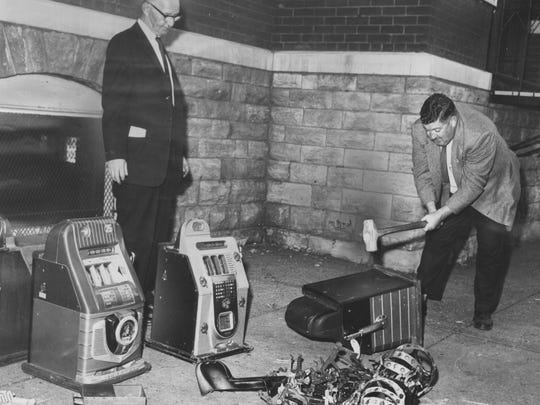 Slots smashed in front of Newport Courthouse on Oct. 25, 1960. Deputies Stan Kemmerling, left, and George Gibson follow judge's order.