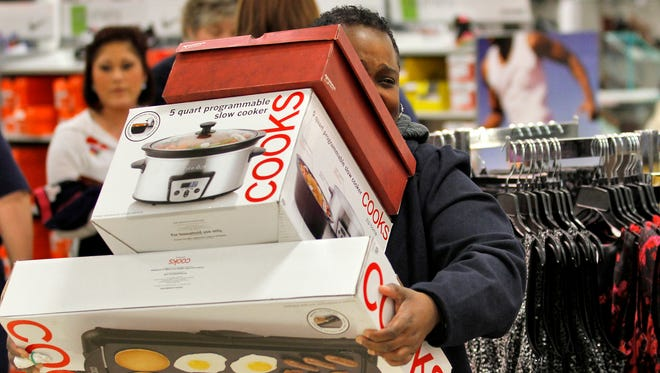 Jackie Beatty takes her purchases to the register during Black Friday sales at JC Penney in 2012.