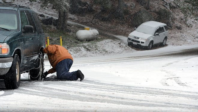 Jerry Walter of Forest Falls, Calif., puts chains on his vehicle before heading to his home in the Southern California mountain community on Dec. 30, 2014.