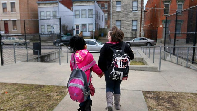 Gymila Jeffreys, 9, and Adrianna Daniels, 9, walk from their after-school program at Olyer School in Lower Price Hill to Community Matters for their weekly Girl Scout meeting.