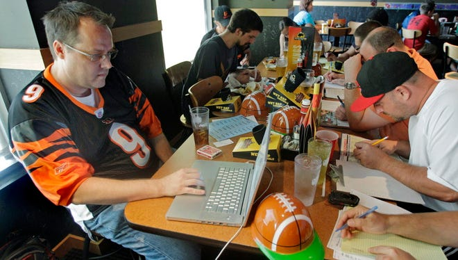 """ORG XMIT: NY154 FILE - This Aug. 30, 2010 file photo shows Brian Sherman, left, using his laptop to record moves in his team's fantasy football draft, at a Buffalo Wild Wings restaurant in Cincinnati. As NFL owners and players wrestle over how to split $9.3 billion in revenue, pro football's lockout has already cut into the widely popular, $800-million per year fantasy football industry.  The pastime's popularity has become far more visible the past few years, with high profile players like Maurice Jones-Drew bragging about drafting themselves, a cable sitcom called """"The League"""" that follows friends playing together and an entire pregame show on ESPN dedicated to fantasy roster decisions. (AP Photo/Al Behrman, FIle)"""