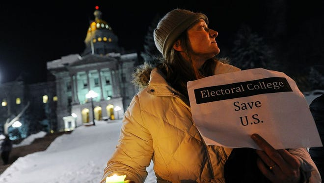 """Ruth Fulton, 44, demonstrates during a candlelight vigil against US President-elect Donald Trump outside the Colorado Capitol building on the eve of the Electoral College vote, in Denver, Colorado on December 18, 2016. """"The Electoral College is supposed to be a safeguard against exactly this sort of person,"""" said Fulton. / AFP / Chris Schneider        (Photo credit should read CHRIS SCHNEIDER/AFP/Getty Images)"""