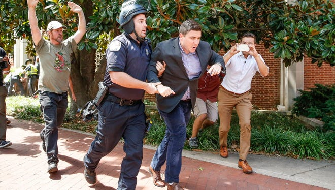 'Unite the Right' rally organizer Jason Kessler is ripped from counter protesters and escorted off Charlottesville City Hall grounds after a 2 p.m. press conference on Aug. 13, 2017.