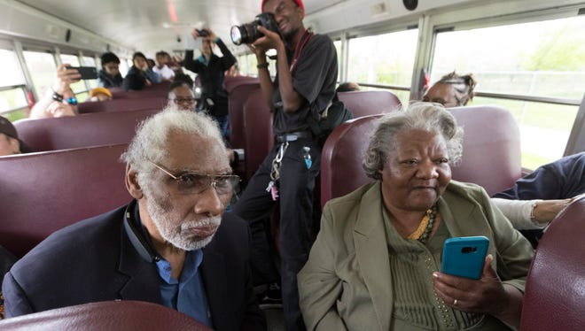 Fred Reed (left) and Betty Harris Martin ride a bus carrying activists from the 1967-'68 open housing marches and others during a stop Saturday at Alice's Garden, 2136 N. 21st St. The 2-acre community garden has more than 125 rental plots for people to grow vegetables and herbs.
