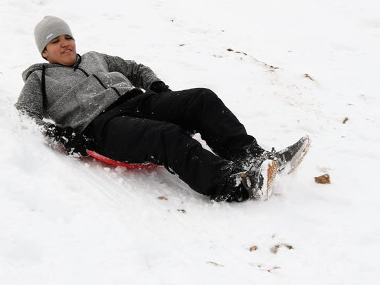 Piedra Vista High School student Albert Garcia, 15, completes a sled run down a hill near the intersection of East 30th Street and College Boulevard Tuesday in Farmington.