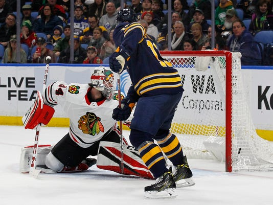 Buffalo Sabres forward Nicholas Baptiste (13) tips the puck past Chicago Blackhawks goalie J-F Berube (34) during the third period of an NHL hockey game, Saturday, March 17, 2018, in Buffalo, N.Y. (AP Photo/Jeffrey T. Barnes)
