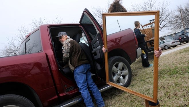 Kenneth Campbell looks over to Betty Alexander who is reflected in a mirror held by Michelle Speers Saturday Feb. 4, 2017 in Cisco. The 6th annual Stacey Watson Memorial Garage Sale was held there Friday and Saturday, the benefit assists families of those fighting illness with bill payments, food and other services.