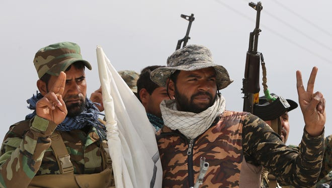 """Members of the Iraqi paramilitary Popular Mobilisation units, which are dominated by Shiite militias, flash the """"V"""" for victory sign after regaining control of the village of Albu Ajil, near the city of Tikrit, from the Islamic State group on March 9, 2015."""