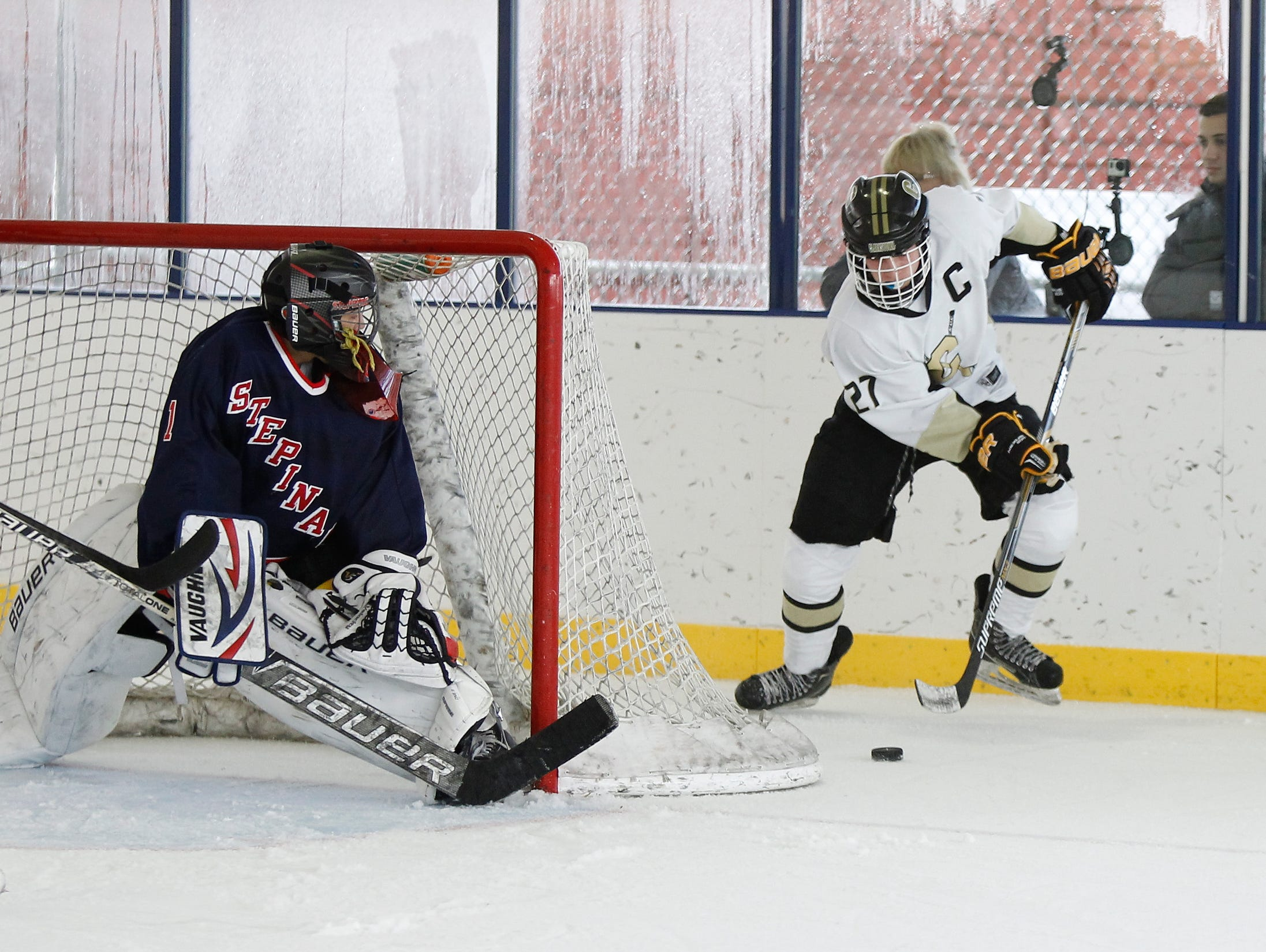 Clarkstown's Adam Marvin (27) works the puck around the net as Stepinac'c goalie Tyler Rosado (1) slides across the crease during a varsity ice hockey game at the 2015 Guy Matthews Thanksgiving Invitational Hockey tournament at Ebersole Ice Rink in White Plains on Friday, Nov. 27, 2015.