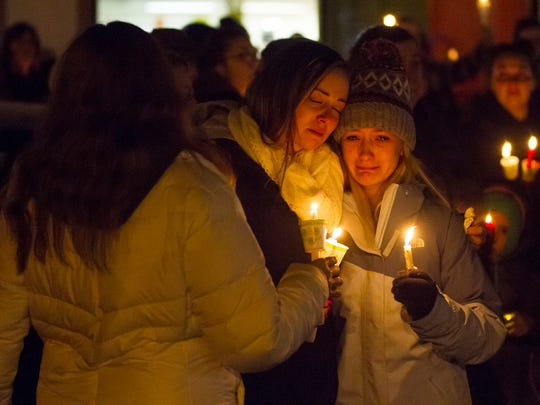 A woman attending a candlelight vigil for Cheryl Myny on Thursday, Nov. 16, 2017, cries as she is comforted by a friend. Myny was shot and killed by her husband inside her Marysville business Jump N Jam last Saturday.