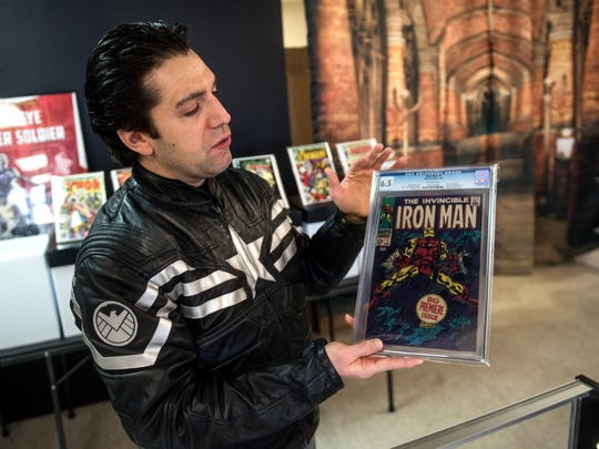 Matthew Madrigale, owner of Kirby Comics, holds up a graded Iron Man comic, one of many in his store, Tuesday, Jan. 9, 2018. Kirby Comics, on York Street, is Hanover's newest comic book store. It opened in December, 2017.