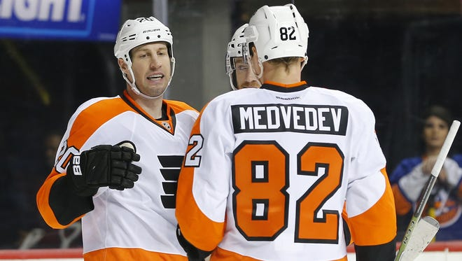 Flyers forward R.J. Umberger (20) celebrates his goal with teammate defensemen Evgeny Medvedev (82) after scoring a goal against the New York Islanders.