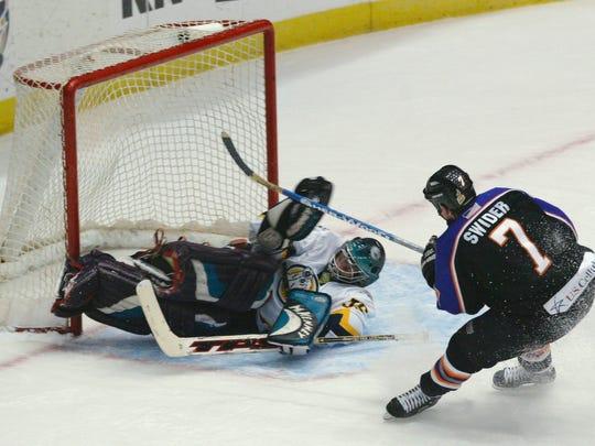 The Knoxville Ice Bears' Kevin Swider scores against Winston-Salem goalie Rick Nichol, Jan. 29, 2005.