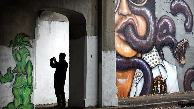 Chris Davis shoots cell phone pictures of the murals covering the walls of the railroad underpass near the intersection of Willett and Lamar where a few of the artworks, which are part of Paint Memphis' annual street and graffiti art project, are generating controversy and withering reviews from City Council members.