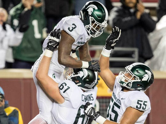 MSU offensive tackle Cole Chewins lifts up running