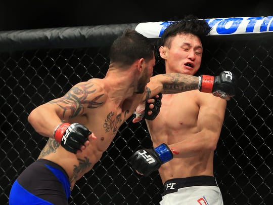 Cub Swanson (L) throws a punch at Doo Ho Choi in their Featherweight bout during the UFC 206 event at Air Canada Centre on Dec. 10, 2016.