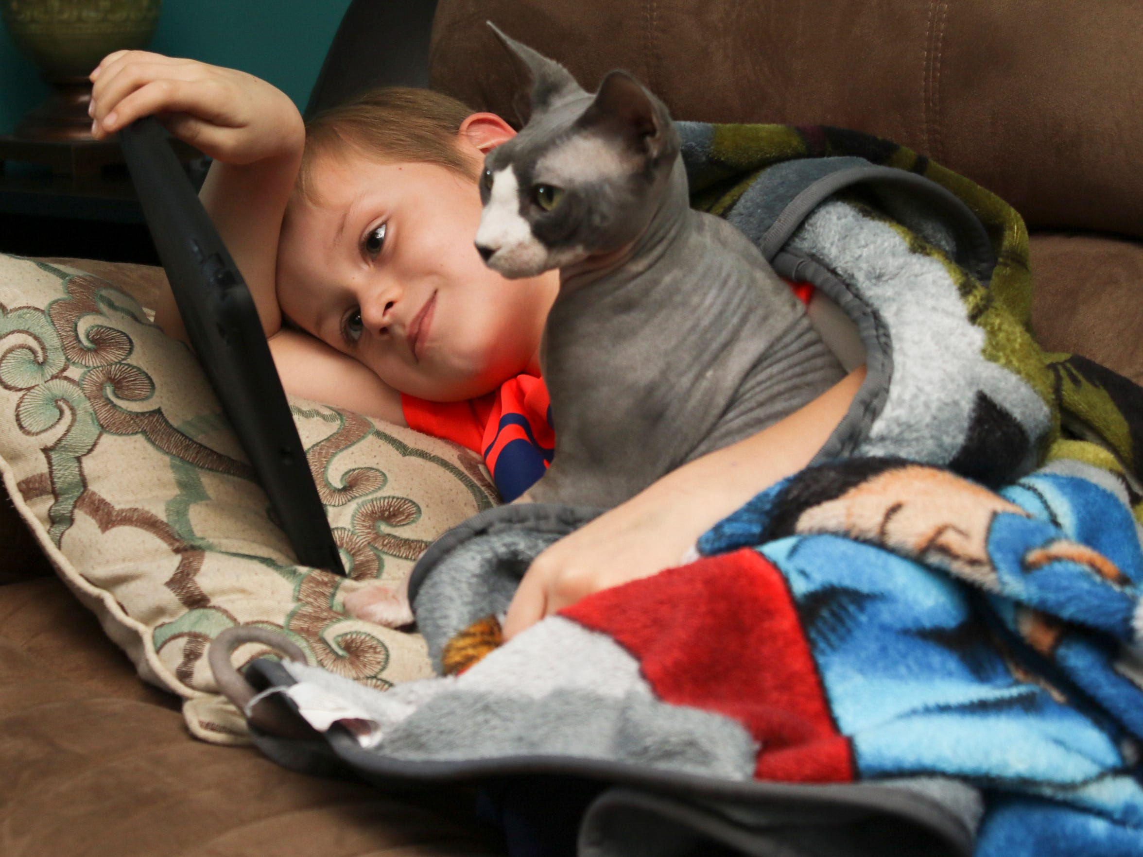 Noah Coffman, 6, watches a video on his iPad with his