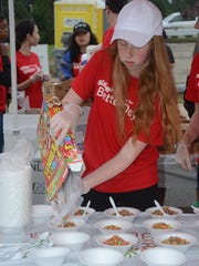 Brittney Honeycutt, 15, pours cereal as the festival begins Saturday morning.