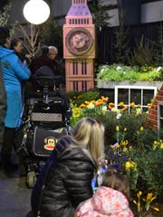 """Vermont Flower Show attendees take in the flower display near a clock tower on March 5, 2017, which was part of the """"Neverland"""" garden display."""