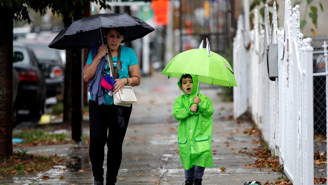 A woman and a child shield themselves from light rain on Tuesday, Oct. 24, 2017, in Newark, N.J.  More stormy weather is forecast for the weekend along the East Coast.